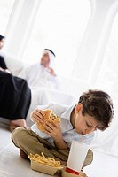 Young boy with fast food in living room with parents in background high key/selective focus
