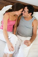 Couple relaxing on bed in bedroom snuggling and smiling selective focus