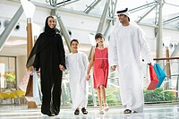 Family walking in mall holding hands and smiling selective focus