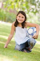 Young girl outdoors at park holding ball and smiling selective focus