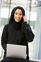 Businesswoman sitting outdoors by building with laptop using cellular phone smiling selective focus