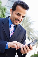 Businessman outdoors using personal digital assistant and smiling high key/selective focus