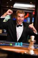 Man in casino winning at roulette and smiling selective focus