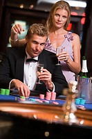 Couple in casino playing roulette and smiling selective focus