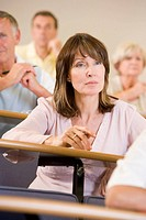 Woman sitting in adult classroom with students in background selective focus