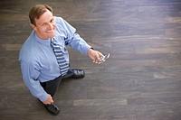 Businessman standing indoors holding cellular phone smiling