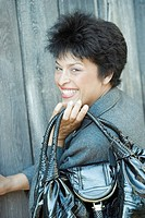 Portrait of a mature woman holding a purse and smiling