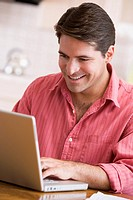 Man in kitchen using laptop smiling
