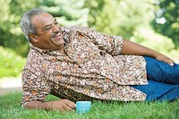 Senior man reclining in a lawn and holding a tea cup