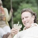 Portrait of a mature man holding a glass of martini and smiling