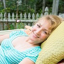 Portrait of a mature woman lying in a hammock and listening to music