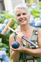 Portrait of a mature woman holding a croquet mallet and a ball
