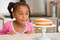 Young girl in kitchen looking at cake on counter