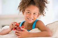 Young girl eating strawberries in living room smiling