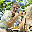 Mature couple having tea in a lawn and smiling