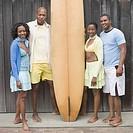 Two couples standing together with a surfboard