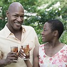 Portrait of a couple holding glasses of ice tea and smiling