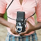 Mid section view of a mid adult woman holding a camera