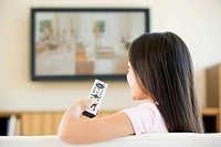 Young girl in living room with flat screen television and remote control