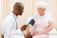 Doctor checking woman´s blood pressure in exam room smiling