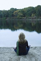 Rear view of a mature woman sitting in lotus position at the lakeside