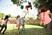 Young girl hitting pinata at birthday party