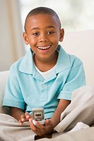 Young Boy Sitting On A Sofa, Text Messaging