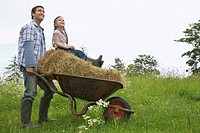 Father pushing daughter 5_6 on wheelbarrow in field