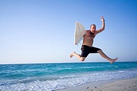 Man jumping with surfboard on beach