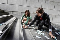 Busines man and woman gathering money on steps