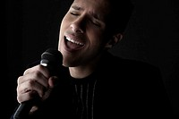 Young man singing into microphone close_up