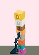 A businessman stacking blocks that spell business