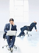 Businessman using a laptop with another businessman reclining on a chair in an office