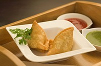 Close_up of two samosas with sauce in a tray