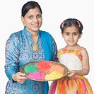 Portrait of a mid adult woman and her daughter holding a plate of powder paint and smiling