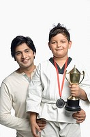 Portrait of a young man with his son holding a trophy