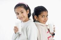 Two girls holding glasses of milk