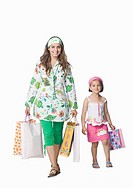 Portrait of a young woman with her daughter holding shopping bags and smiling