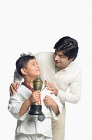 Boy holding a trophy and looking at his father