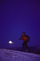 A man running on an alpine ridge in winter near Mount Judah CA