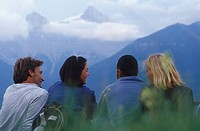Four friends sitting in mountain meadow three Sisters Mountain behind CANADA Alberta