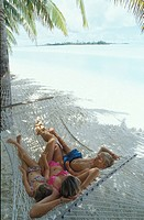 Mother relaxaing with two kids on hammock white sand beach and lagoon behind COOK ISLANDS Aitutaki