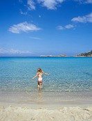 Girl 7 entering water shallows at Spiaggia Blanca near Santa Teresa Gallura ITALY Sardinia