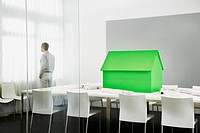 Small green model house on conference table