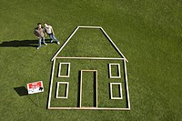 "Couple standing near ""for sale"" sign and house outline (thumbnail)"