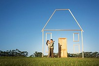 Couple hugging next to vertical house outline