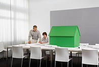 Business people with small model house on conference table