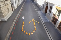 Man standing with traffic cones in shape of u_turn