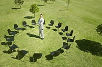 Businessman standing in circle of office chairs in field