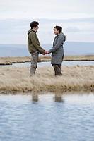 Teenage couple holding hands near stream